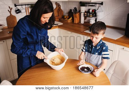kid boy preparing dough for muffins with mother in kitchen. Happy family cooking together in weekend morning