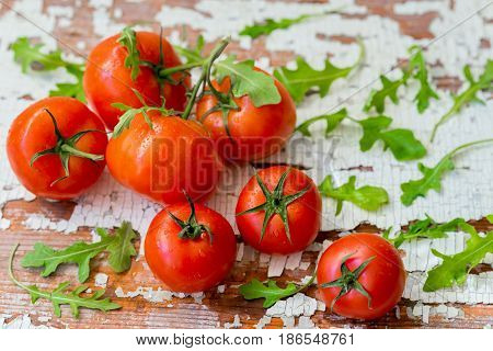 Fresh organic ripe tomatoes with water drops, basil leaves on wooden old shabby vintage table. Top view with copy space. Healthy food concept, antioxidant, diet