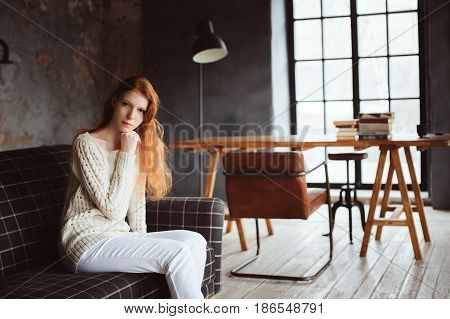 portrait of dreamy young beautiful redhead woman relaxing at home in cozy autumn evening