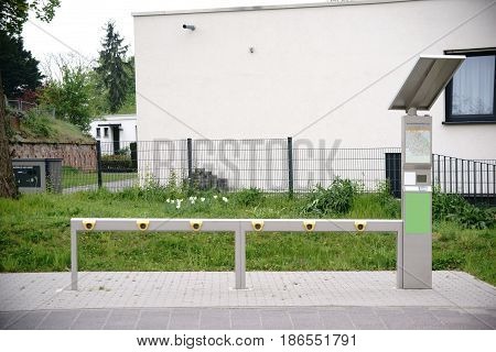The empty stations of a bicycle rental system with solar panels and a map.