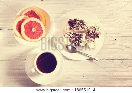 Breakfast on a light table. The top view meringue segments of a grapefruit and coffee on a table from light boards. It is toned vintage style
