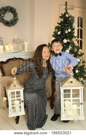 Woman sitting in armchair and little son holds big lanterns in room with christmas tree