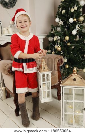Happy little boy in santa costume and felt boot holds big lantern in room with christmas tree
