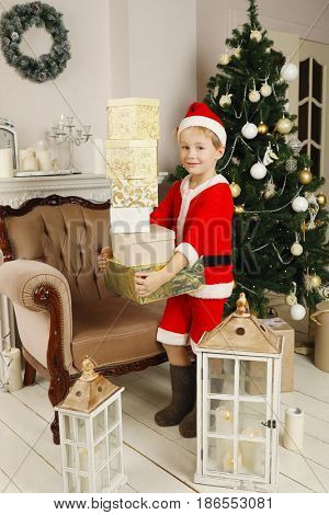 Little boy in santa costume and felt boot holds gifts in room with christmas tree