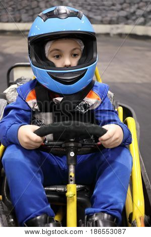 Little funny boy in helmet prepares for driving competition kart