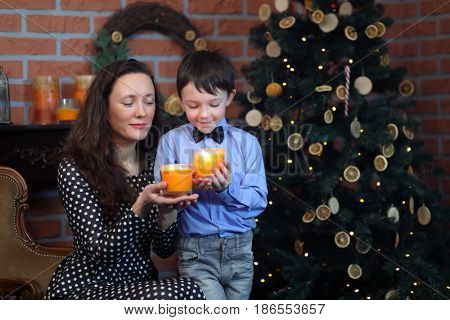 Woman and her little son hold candles in glasses near christmas tree in brick room