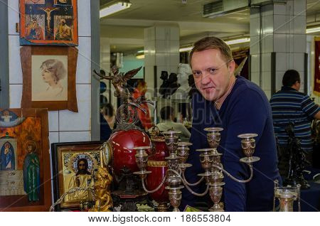 Moscow, Russia - March 19, 2017: Seller of rare icons and valuable antiques at a special market is waiting for buyers-collectors