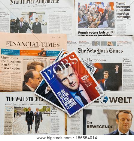 PARIS FRANCE - MAY 10 2017: l'Obs magazine above multiple international newspapers front page covers with the picture of the newly elected French president Emmanuel Macron the 8th President of France