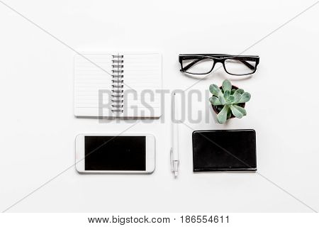 office desk design with mobile, notebook and glasses on white background top view space for text