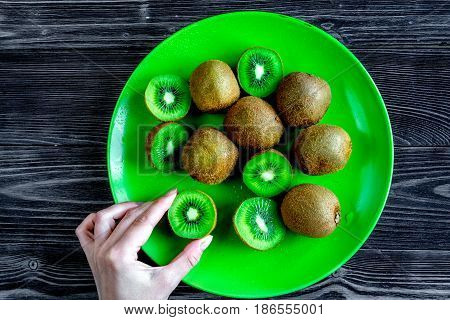 exotic fruit design with green kiwi on dark wooden background top view