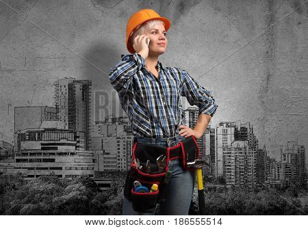 Engineer woman talking mobile phone and sketches of construction project on wall
