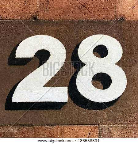 Number 28 twenty eight black and white house number address sign painted on red stone wall textured background