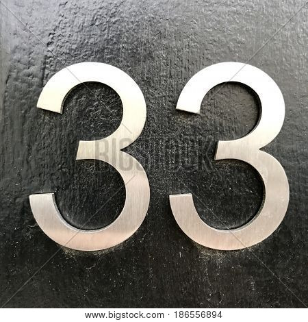 Number 33 thirty three silver metal house number address sign screwed into painted black wood fence textured background