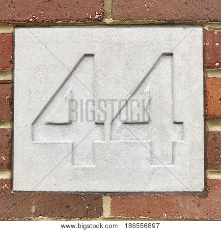 Number 44 forty four carved stone house number address sign screwed into painted white stone wall textured background