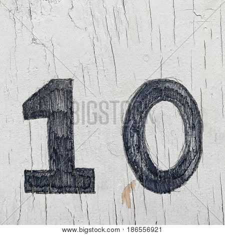 Number 10 ten house number address sign painted one white wood fence textured background