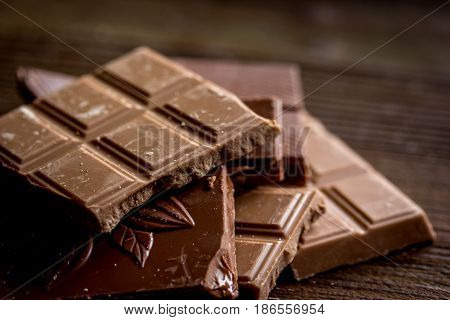black and milk chocolate pieces on wooden table background