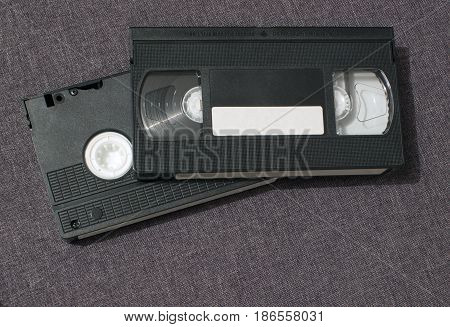 Two video cassettes lie one on top of the other on a gray background