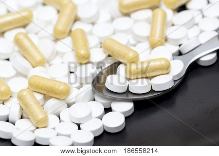 Medicine pills on a surface with a doseage in a teaspoon