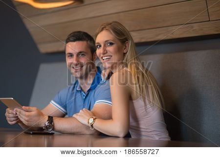 Young couple using tablet computer at luxury home together, looking at screen, smiling.
