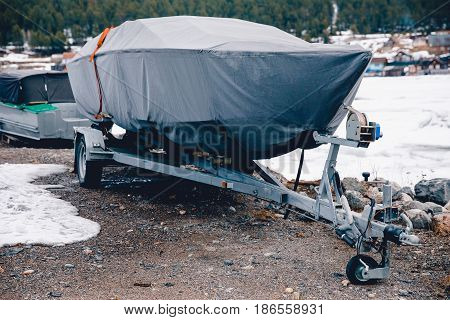 boat is covered with a tent, Cover, case against rain, snow and mud.. Warehouse on the boat pier. Concept training of boats, ships for the winter in the home.