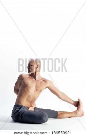 The yoga man sitting in the strange pose on the white background