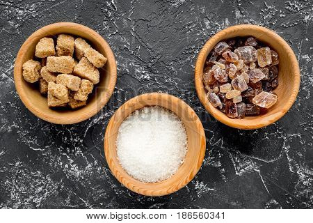 lumps of sugar with bowls sweet set on dark kitchen table background top view