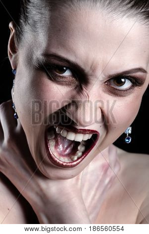 luxury woman shouts smothers herself looking at camera on black background