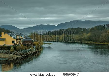 House on the riverbank in the rural Irish landscape, Kerry county, Ireland