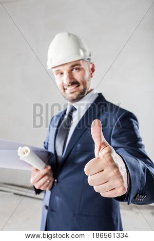 Businessman showing OK gesture, approving the building progress. Real estate, housing development and building industry.