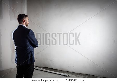 Businessman standing in an open empty space indoors and looking at the wall. Concept of business vision, startup, planning. Copyspace for your text, desing.