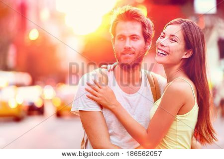 Young happy interracial couple in sunshine flare enjoying sunset relaxing having fun on urban city street in New York city, USA. Playful multiracial people living a modern lifestyle.