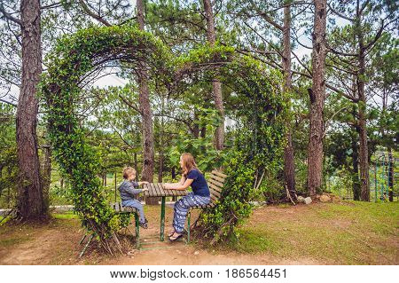 Mother And Son Under A Bush In The Form Of A Heart. St. Valentine's Day, Love Concept
