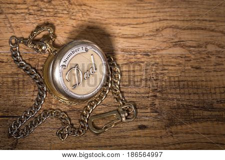 Gold pocket watch on a wooden surface