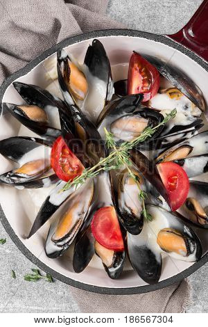 Cooked mussels in a pan served on a napkin garnished with tomatoes and thyme. Steamed mussels in white wine sauce. Seafood mussels on pan with cream sauce. Close up. top view.