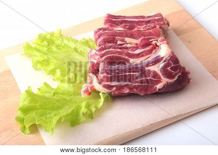 Raw beef edges and lettuce leaf on wooden desk isolated on white background from above and copy space. ready for cookin