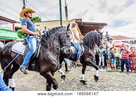 San Juan del Obispo, Guatemala - June 12 2016: Cowboy & cowgirl ride horses in horse street parade in village near Antigua, Guatemala