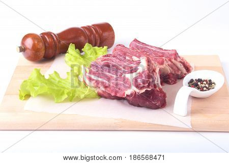 Raw beef edges, lettuce leaf, pepper grinder and spices on wooden desk isolated on white background from above and copy space. ready for cooking