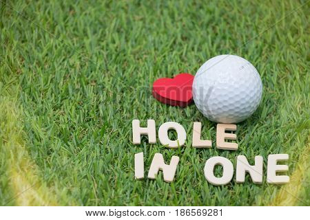 Hole in one of golf word with golf ball on green grass