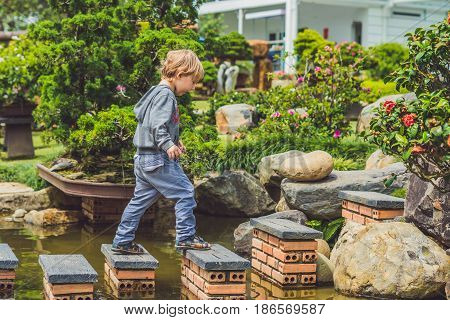 Adorable Young Boy With Crossing River Or Water Jumping From Rock To Rock. Crossing The Gap, Freedom