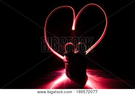 Two Young Lovers Paint A Heart On Fire. Silhouette Of Couple And Love Words On A Dark Background