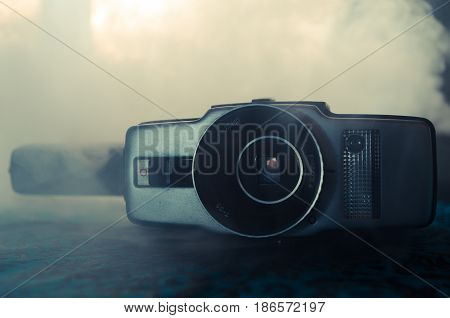 Classic vintage old 8mm movie camera on table with fog close up. Selective focus