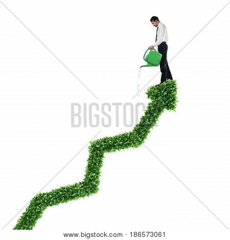 Businessman watering a big plant that grows like an arrow