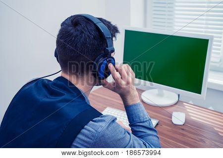 Portrait of handsome man speacking in call center office with headphones near PC computer. Copyspace on Chromakey screen