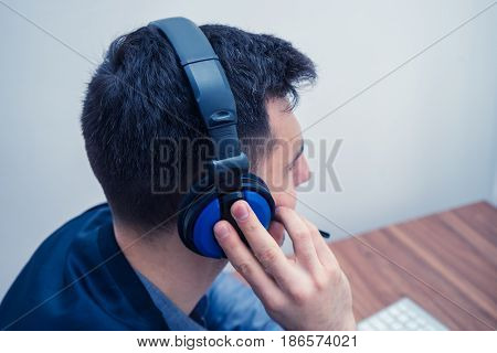 Portrait of handsome man speacking in call center office with headphones