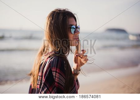 young stylish happy hipster woman traveling around the world wearing aviator sunglasses, denim shirt, tropical island lagoon vacation.