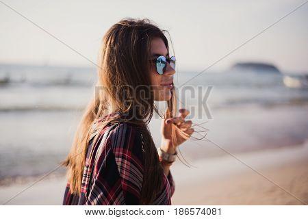 young stylish happy hipster woman traveling around the world wearing aviator sunglasses, denim shirt, tropical island lagoon vacation.