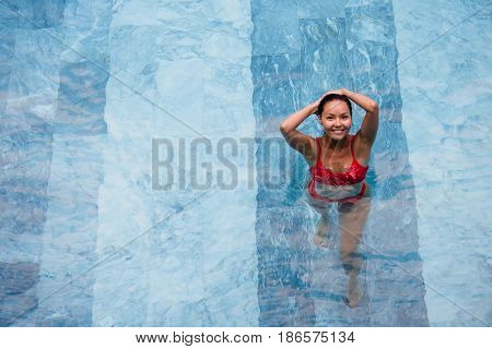 Enjoying vacation. Smiling beautiful young woman in swimming pool