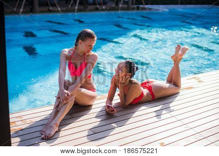 Two attractive blonde and brunette girls with long hair are lying on flor near pool. They wear bikini and swimsuit. They are smiling and look enjoyed. View from above