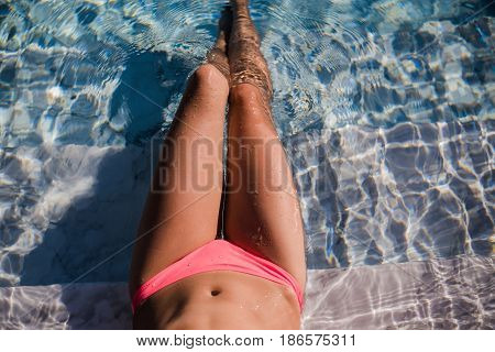 Female sexy tanned wet legs into water at pool