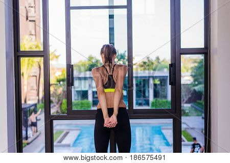 Back view of young woman stretching doing morning workout at luxury hotel resort with a great view. Female model doing side bending exercises and looking at poolside scenery in the window.